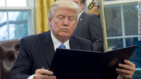 US President Donald Trump reads an executive order withdrawing the US from the Trans-Pacific Partnership prior to signing it in the Oval Office of the White House in Washington, DC, January 23, 2017. Trump signed the decree Monday, effectively ending US participation in a sweeping trans-Pacific free trade agreement negotiated under former president Barack Obama. / AFP / SAUL LOEB        (Photo credit should read SAUL LOEB/AFP/Getty Images)