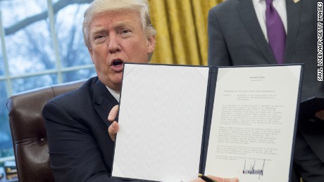 President Donald Trump holds up an executive order withdrawing the US from the Trans-Pacific Partnership after signing it in the Oval Office of the White House in Washington, DC, January 23, 2017.
