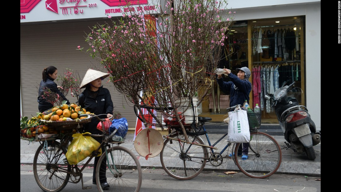Vendors sell peach blossoms along a street in Hanoi, Vietnam, on Monday, January 23.