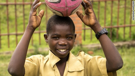 A smiling child balances a rugby ball on his head.