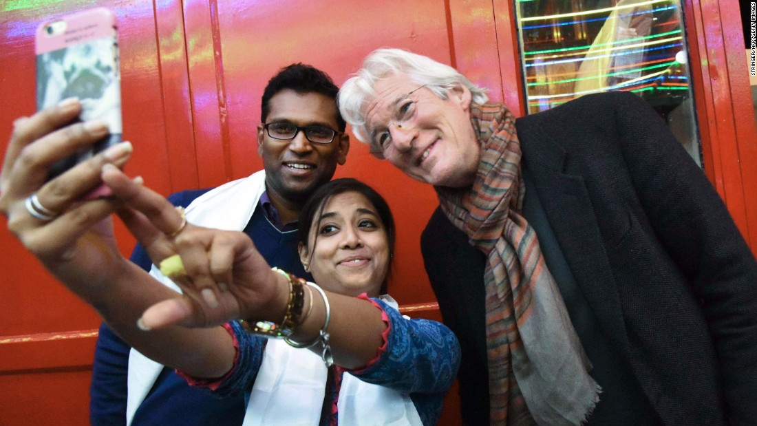 A fan takes a photo with actor Richard Gere, right, at a Buddhist meditation center in Bodh Gaya, India, on Thursday, January 12.