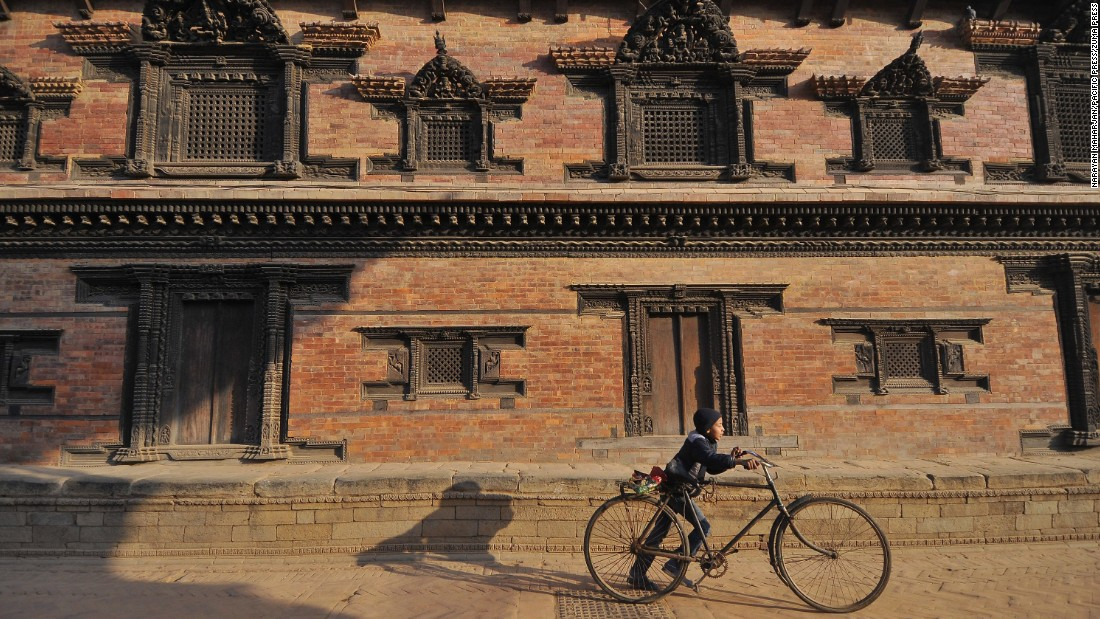 <strong>Kathmandu, Nepal:</strong> A child wheels his bike through UNESCO World Heritage site Bhaktapur Durbar Square, a former royal plaza filled with temples, statues and other landmarks.