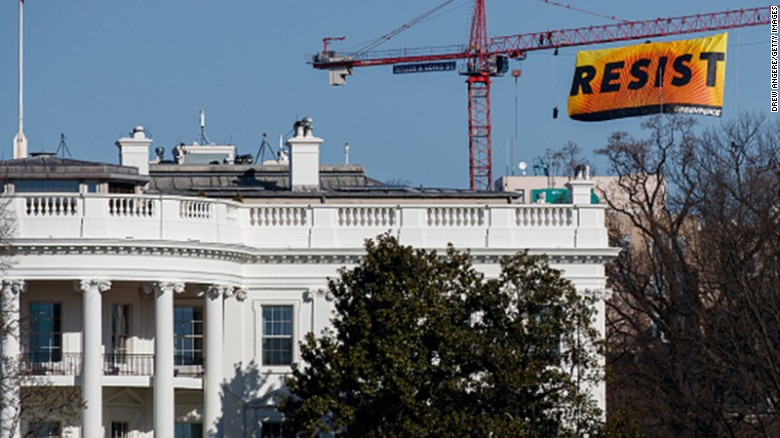 WASHINGTON, DC - JANUARY 25: With the White House in the foreground, protesters unfurl a banner atop a crane at the construction site of the former Washington Post office building, January 25, 2017 in Washington, DC. The protestors are with the Greenpeace organization.