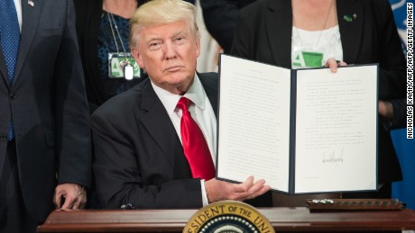 US President Donald Trump signs an executive order to start the Mexico border wall project at the Department of Homeland Security facility in Washington, DC, on January 25, 2017. / AFP / NICHOLAS KAMM        (Photo credit should read NICHOLAS KAMM/AFP/Getty Images)