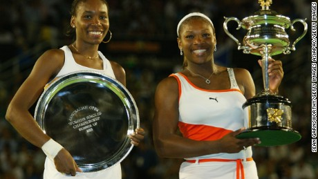 Serena Williams R) holds the winners trophy and her sister Venus Williams holds the runners up trophy after the women's singles final during the Australian Open at Melbourne Park on January 25, 2003.