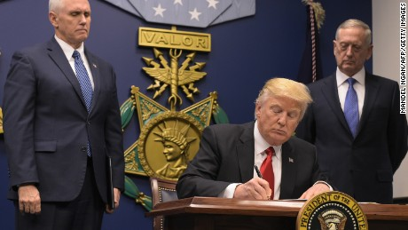 US President Donald Trump signs an executive order alongside US Defense Secretary James Mattis and US Vice President Muike Pence on January 27, 2016 at the Pentagon in Washington, DC.