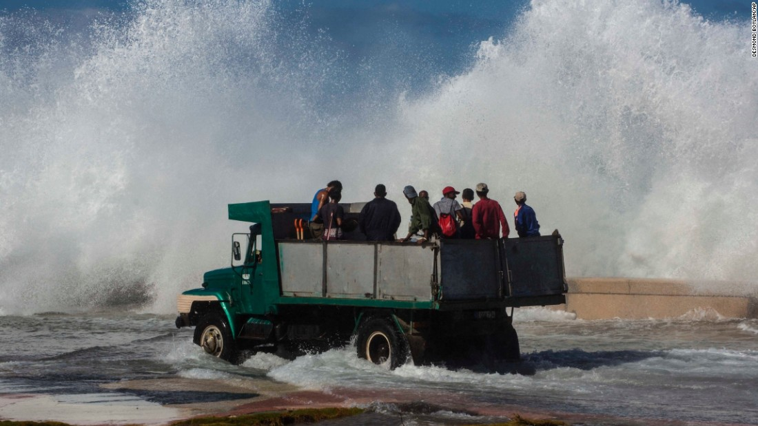 A wave crashes into a sea wall in Havana, Cuba, as a dump truck carries cleaning workers on Tuesday, January 24. Because of high winds and tides, there was some flooding in parts of Havana's Vedado neighborhood.