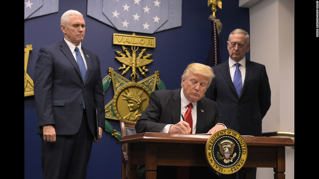 "President Trump, flanked by Vice President Pence and Defense Secretary James Mattis, signs an executive order to begin what he called a ""great rebuilding of the Armed Services"" on Friday, January 27. Trump added that the executive action instructs Mattis to begin ""developing a plan for new planes, new ships, new resources and new tools for our men and women in uniform."""