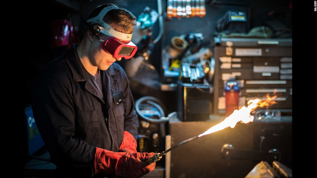 Hull Maintenance Technician Fireman Clayton Karpi lights an acetylene torch aboard the USS Theodore Roosevelt on Wednesday, January 25. The aircraft carrier was off the coast of Southern California.
