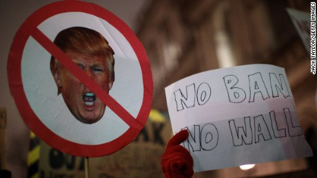 LONDON, ENGLAND - JANUARY 30: Demonstrators hold up placards during a protest outside Downing Street against U.S. President Donald Trump's ban on travel from seven Muslim countries on January 30, 2017 in London, England. President Trump signed an executive order on Friday banning immigration to the USA from seven Muslim countries. This led to protests across America and, today, in the UK, a British petition asking for the downgrading of Trump's State visit passed one million signatures this morning. (Photo by Jack Taylor/Getty Images)