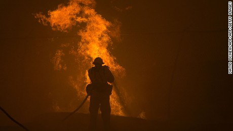 TOPSHOT - A firefighter hoses down burning pipes near a water tank at the Sand Fire on July 23 2016 near Santa Clarita, California. Fueled by temperatures reaching about 108 degrees fahrenheit, the wildfire began yesterday has grown to 11,000 acres. / AFP / DAVID MCNEW        (Photo credit should read DAVID MCNEW/AFP/Getty Images)