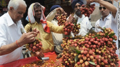 A fruit vendor offers lychees to customers from his roadside stall in Amritsar, India.