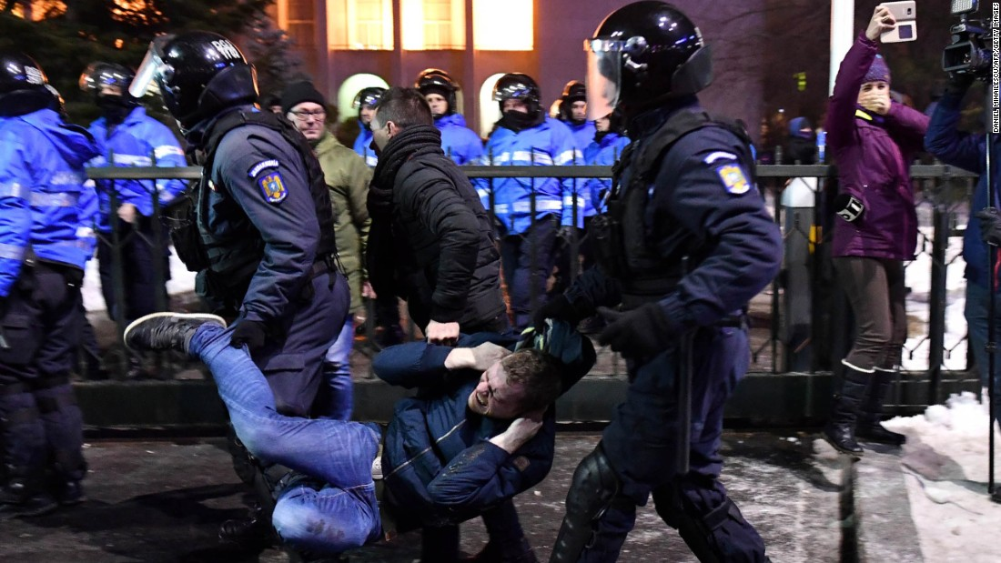 Anti-riot police remove a protester February 1 in front of government headquarters in Bucharest.