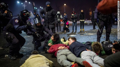 Riot police detain some protesters Wednesday in Bucharest.