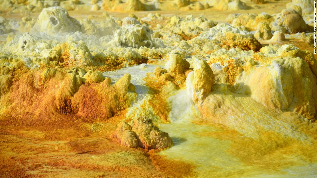 Temperatures average 34.5 degrees Celsius but have risen to over 50 degrees. Rocks are colored by minerals and algae.