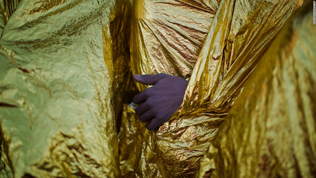 A migrant's hand is seen outside a blanket while on the deck of the Golfo Azzurro rescue vessel after arriving at the port of Messina, Italy, on Sunday, January 29.