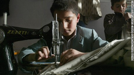 KABUL, AFGHANISTAN - NOVEMBER 5:  Mohammad Elais, age 13, sews a pair of pants while Mustafa(R) age 7 checks some stitching at the Sajaad Tailor shop November 5, 2004 in Kabul, Afghanistan. Elias works with 4 other boys at the small tailor shop coming after school every day. He makes less than a dollar a day. Many Afghan children are forced to work because they must help support their poverty stricken families. (Photo by Paula Bronstein/Getty Images)