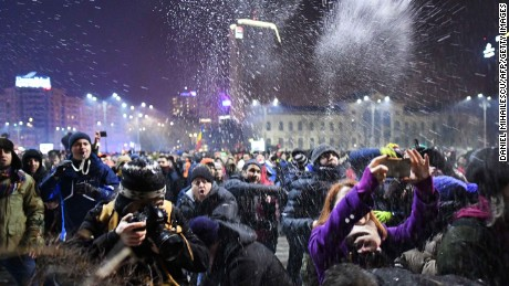 People throw snow toward  police guarding government headquarters in Bucharest.