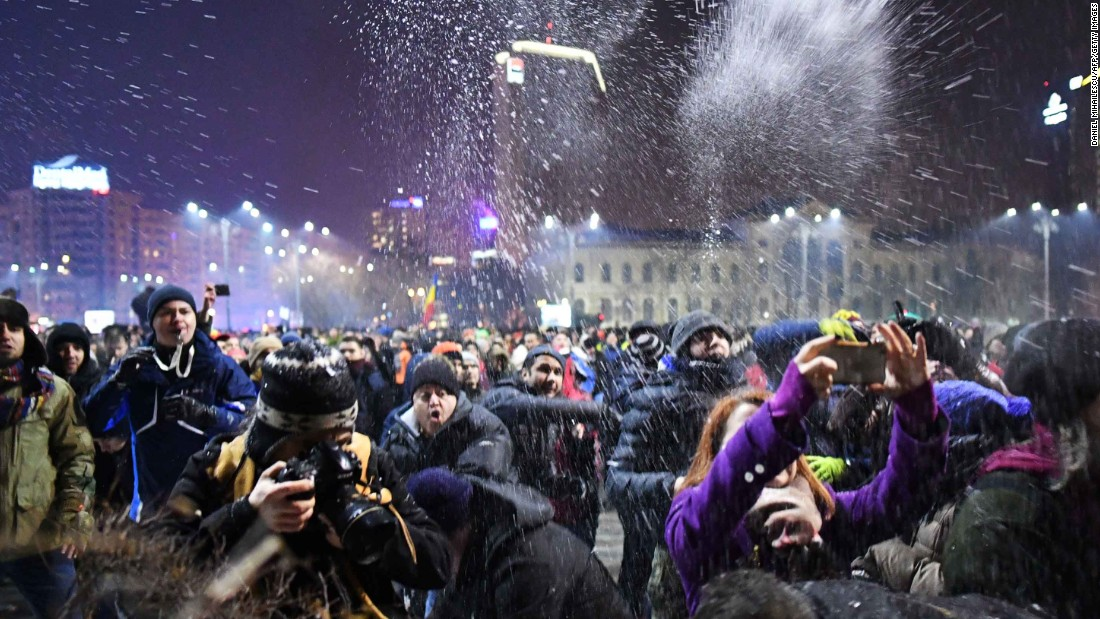 People throw snow at police protecting government headquarters on January 31 in Bucharest. Protesters also took to the streets in other cities across Romania.