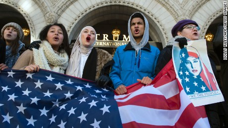 Protesters hold an US Flag while protesting outside the Trump Hotel on February 4, 2017, in Washington, DC. The demonstrators protested US President Donald Trump's travel ban on nationals from seven Muslim-majority countries.