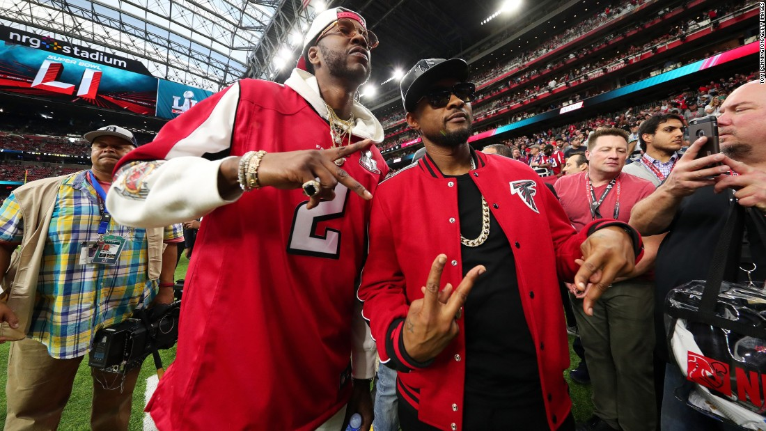 Rapper 2 Chainz, left, and R&B singer Usher pose for a photo before the game.