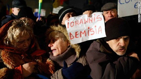 Protests continued in Bucharest on Monday evening - this demonstrator's sign calls for the president to quit.