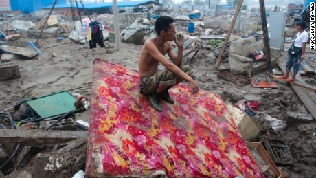 A man rests by his destroyed home in the devasted area of Beijing in July 2012, after severe flooding.