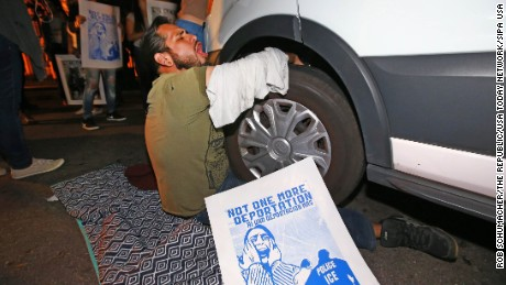 A protester locks himself to the van carrying Garcia de Rayos away.