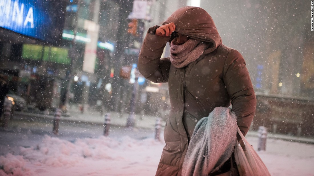 A woman braces against the wind-blown snow in Times Square.