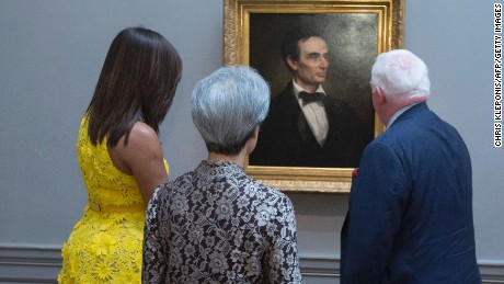 "First Lady Michelle Obama and Ho Ching(C), wife of Singapore's Prime Minister Lee Hsien Loong look at a portrait of the 16th President of the US, Abraham Lincoln as they are escorted through the National Gallery of Art in Washington DC, August 2, 2016 by Museum Director Earl ""Rusty"" Powell III."