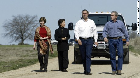 US President George W. Bush (R) walks with Mexican President Vicente Fox (2R) as they arrive for a press briefing joined by their wives First Lady Laura Bush (L) and Marta Fox (2L)  after a morning b-lateral meeting at Bush's 1600 acre ranch 06 March 2004 Crawford, Texas.