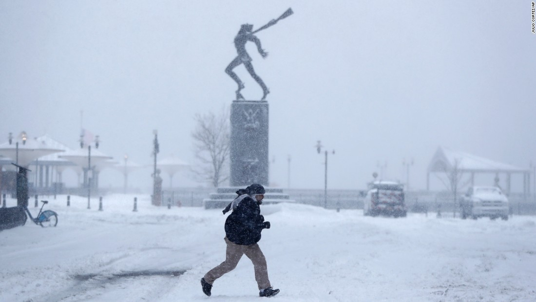 A person runs across a snow-covered area in Jersey City, New Jersey, on February 9.