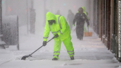 Workers clean the sidewalk on Boylston St. as a winter storm bears down on February 9, 2017 in Boston, Massachusetts. A snowstorm has been forecast with up to a foot of snow in a large swath of the Northeast today.