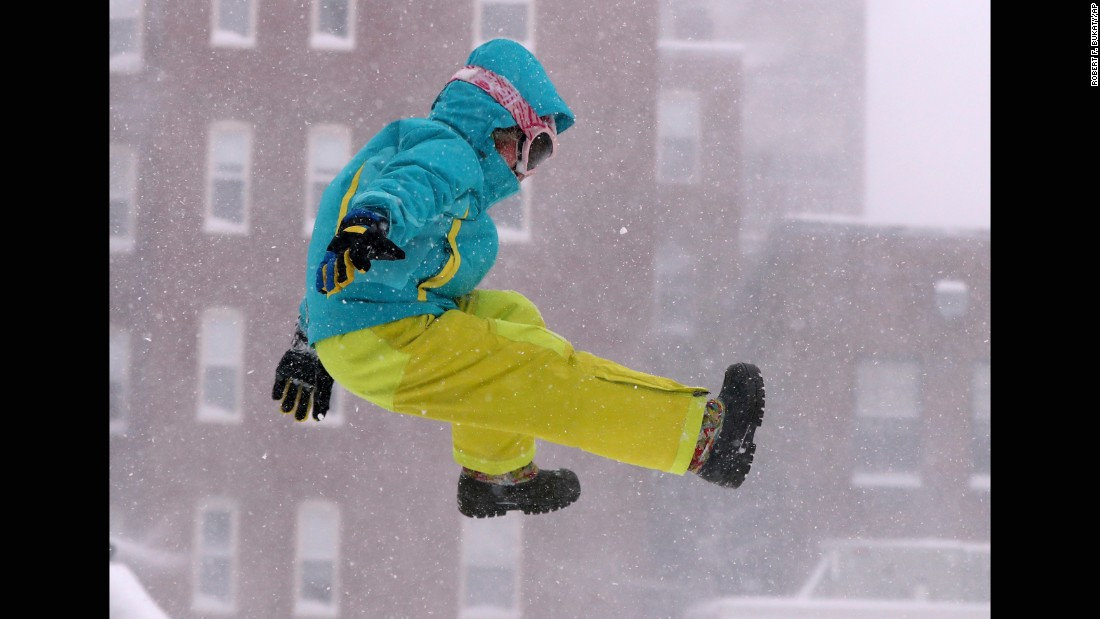Carina Stack jumps from a snowbank while playing in Portland, Maine, on February 9.
