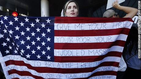 "Chella, from Sherman Oaks, holds the U.S. flag with words from the sonnet, ""The New Colossus,"" by poet Emma Lazarus  while joining people who continue to protest President Donald Trump's travel ban at the Tom Bradley International Terminal at LAX on January 29, 2017 in Los Angeles, California."