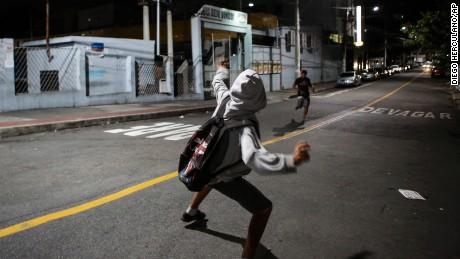 A man readies to throw a rock at a supermarket in Vitoria, Espirito Santo state, Brazil, Tuesday, February 7, 2017. More than 1,000 army troops patrolled the streets of the southeastern Brazilian city of Vitoria amid a crime wave that left at least 70 people dead over two days, authorities said.