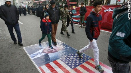 Iranians march on a portrait of Trump in Tehran on Friday.