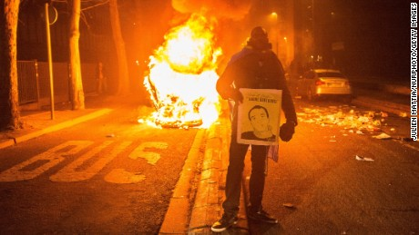 A man stands in front of a burning vehicle on Saturday amid protests in the Bobigny suburb of Paris.