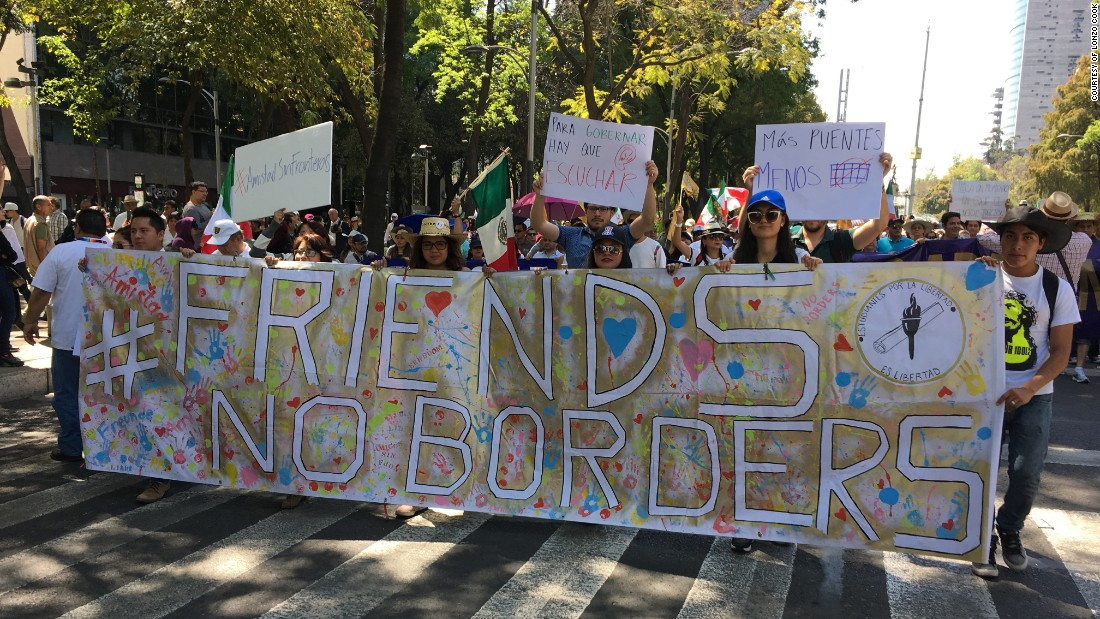 "Protesters hold a banner that reads ""#Friends, No Borders."" Additional signs from left to right: ""#friendship with no borders,"" ""to govern you have to listen,"" ""Less walls."""