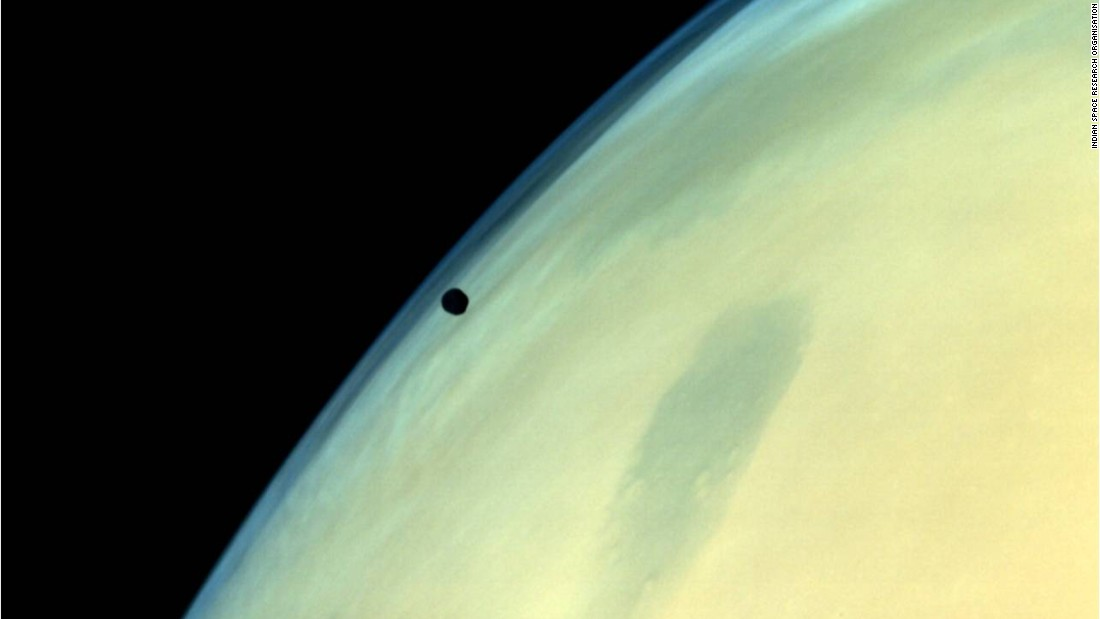 Phobos, one of the two natural satellites of Mars, silhouetted against the Martian surface.
