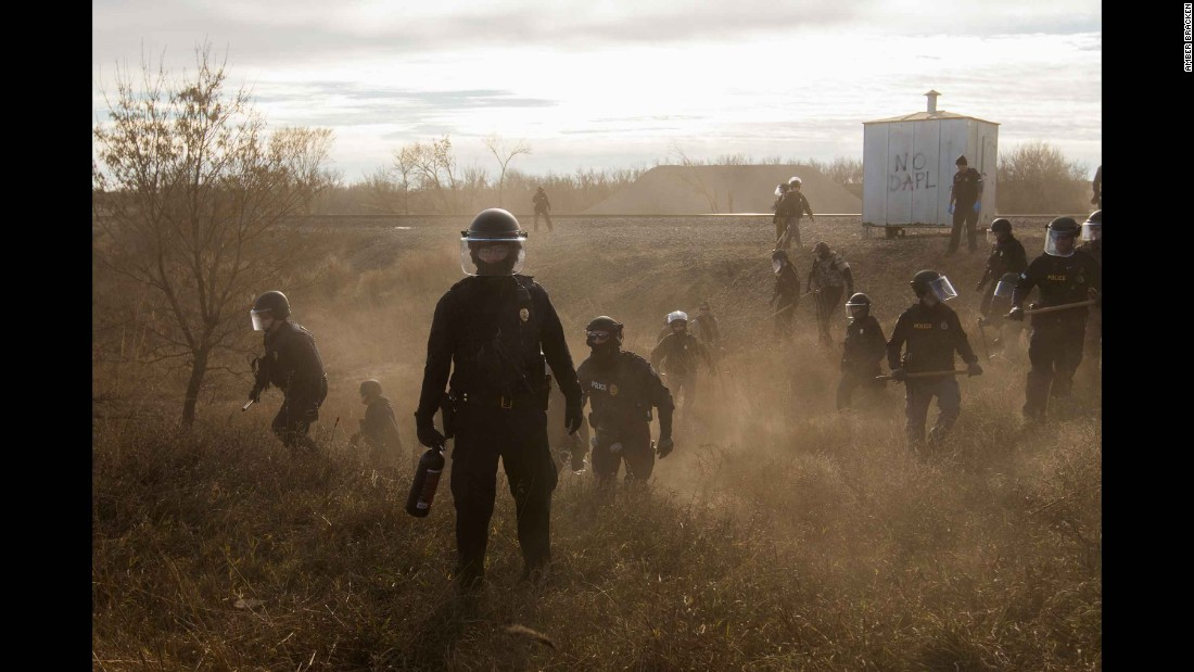 "Riot police clear protesters from a secondary road outside a Dakota Access Pipeline worker camp. The <a href=""http://www.cnn.com/2016/09/07/us/dakota-access-pipeline-visual-guide/"" target=""_blank"">Dakota Access Pipeline</a> is a $3.7 billion project that would cross four states and change the landscape of the US crude oil supply. But the Standing Rock Sioux tribe says the pipeline would affect its drinking-water supply and destroy its sacred sites."