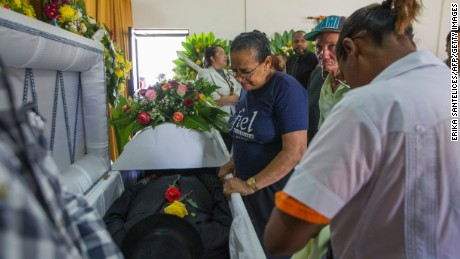 Relatives of broadcaster Luis Manuel Medina mourn next to his coffin in the Dominican Republic.