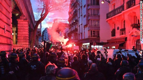 A smoke flare lights up the crowd at an anti-police protest in Paris.