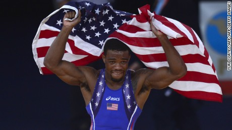 US' Jordan Ernest Burroughs celebrates with national flag after defeating Iran's  Sadegh Saeed Goudarzi in their Men's 74kg Freestyle gold medal match on August 10, 2012 during the wrestling event of the London 2012 Olympic Games.   AFP PHOTO / YURI CORTEZ        (Photo credit should read YURI CORTEZ/AFP/GettyImages)