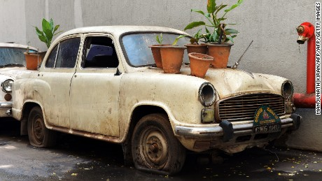 "An old defunct Ambassador ""State Car"" hosts plant bearing pots at the basement of a government building in Bangalore on May 30, 2014 -- the year production was stopped."
