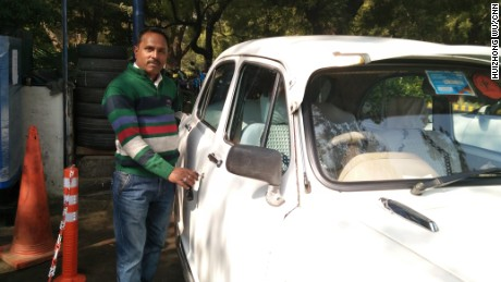 Rajkumar Kapoor, a driver in Delhi, stands with the Ambassador car that he drives.