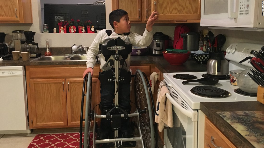 Jason opens a kitchen cupboard, December 9, 2016.  His adoptive parents, Brian and Jeri Wilson, are building a new home that's wheelchair accessible.