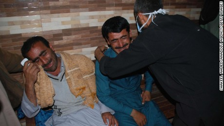 Men at a Sehwan, Pakistan, hospital mourn their relatives' deaths after a suicide attack Thursday.