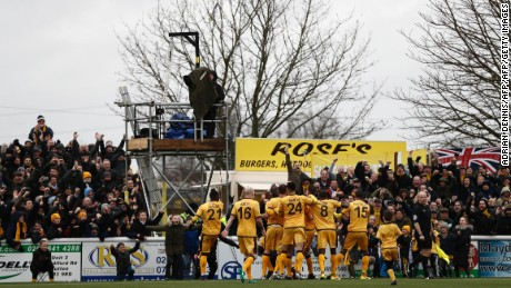 Sutton United players celebrate scoring the winning goal against Leeds United in the fourth round.