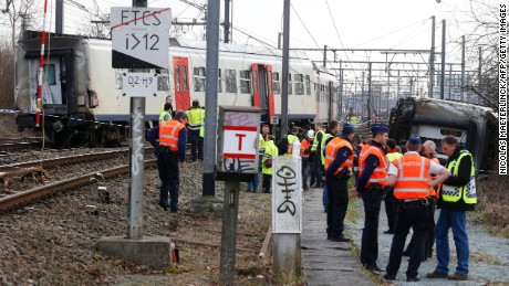 Police officers and officials stand next to a train after it derailed Saturday in Leuven, east of Brussels.